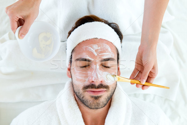 Man with clay facial mask in beauty spa.  Stock photo © nenetus