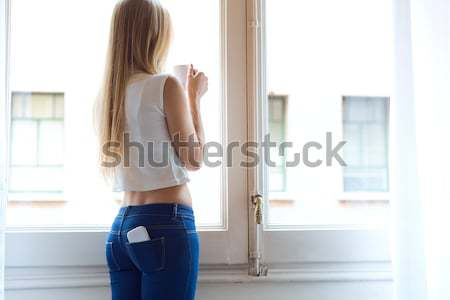 Young beautiful woman at home with mobile phone in back pocket. Stock photo © nenetus
