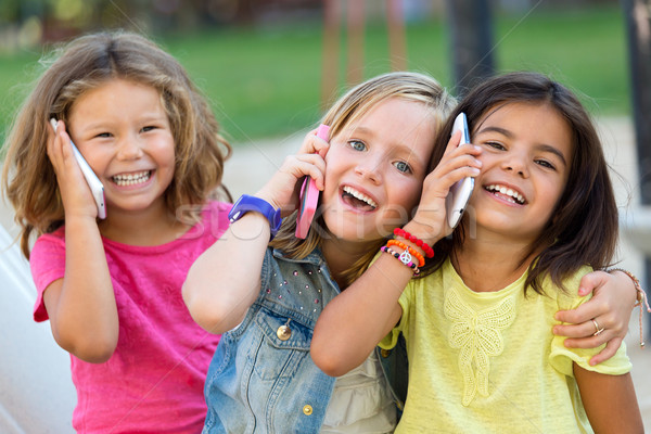 Group of childrens using mobile phones in the park. Stock photo © nenetus
