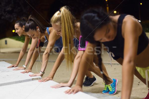 Group of girls doing push-ups at night. Stock photo © nenetus