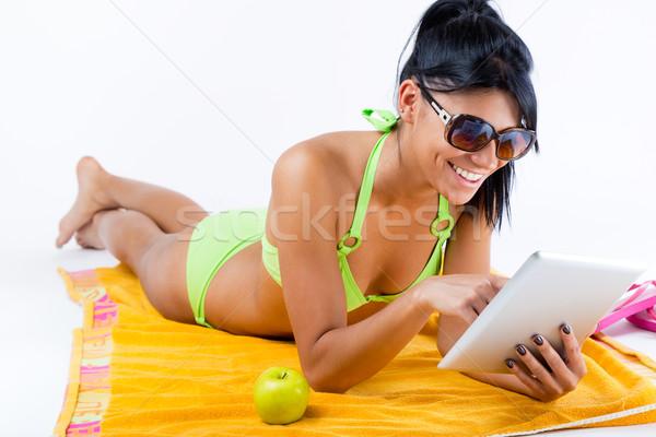 Happy young girl with green bikini and digital table Stock photo © nenetus