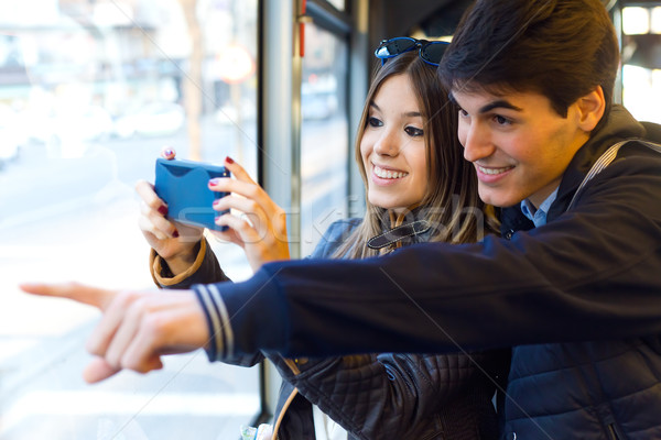Young couple taking selfies with smartphone at bus. Stock photo © nenetus