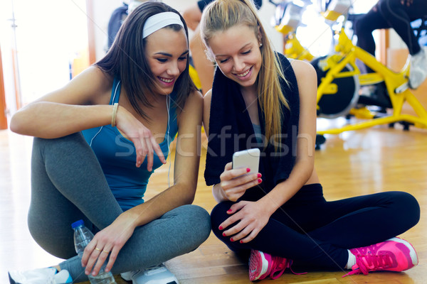 Young women using mobile phone in the gym. Stock photo © nenetus