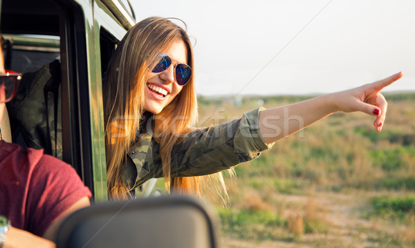 Portrait of beautiful girl on car roadtrip pointing forward.  Stock photo © nenetus