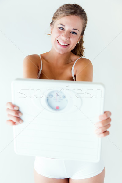 Stock photo: Young girl in underwear holding scales.
