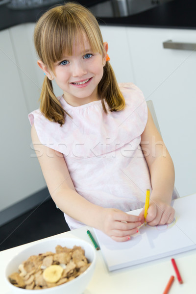 Child drawing with crayons, sitting at table in kitchen at home Stock photo © nenetus