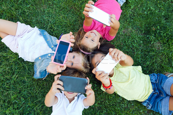 Stock photo: Group of childrens taking a selfie in the park.