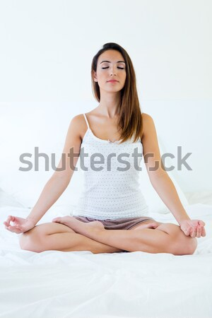Beautiful young woman doing yoga exercises. Stock photo © nenetus
