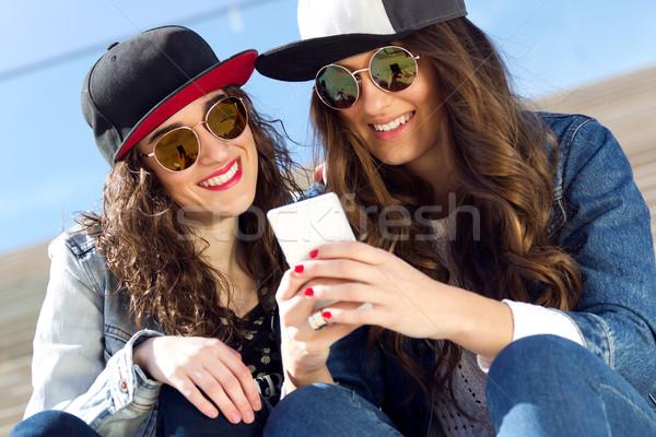 Two girls having fun with smartphones Stock photo © nenetus