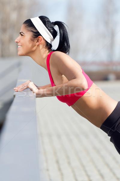 Stock photo: Young woman doing push-ups