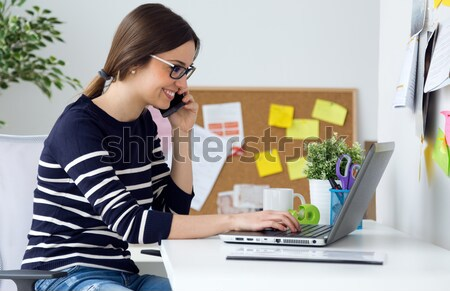 Confident young woman working in her office with laptop. Stock photo © nenetus