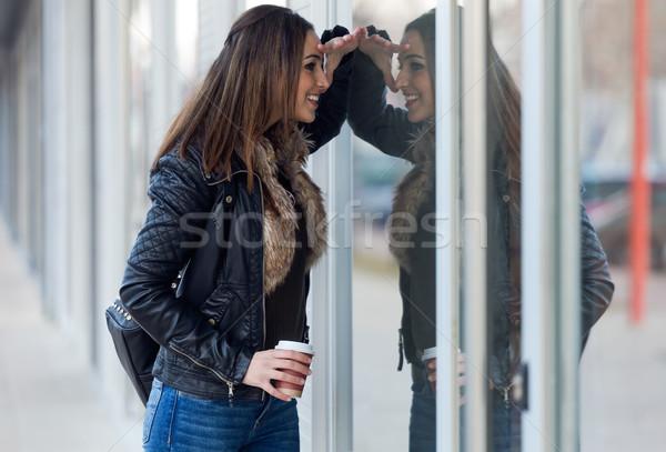 Young beautiful woman looking at the shop window. Stock photo © nenetus