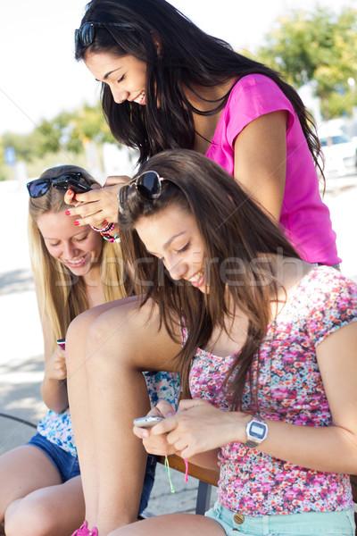 Drie meisjes smartphones park vrouwen Stockfoto © nenetus