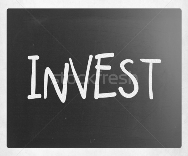 'Invest' handwritten with white chalk on a blackboard Stock photo © nenovbrothers