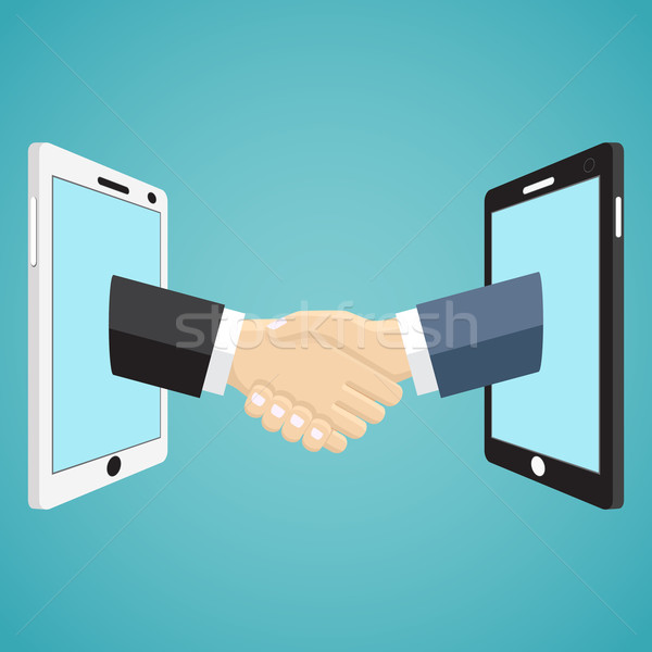 Handshaking businessmen hands from mobile phones. Stock photo © Neokryuger