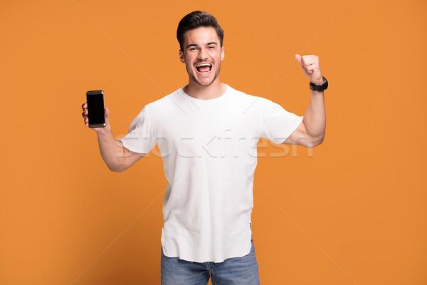 Lächelnd schöner Mann Handy gelb gut aussehend aufgeregt Stock foto © NeonShot