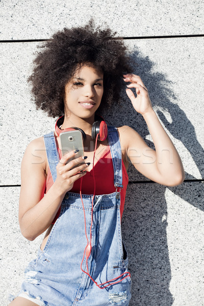 Kız afro cep telefonu genç kulaklık Stok fotoğraf © NeonShot