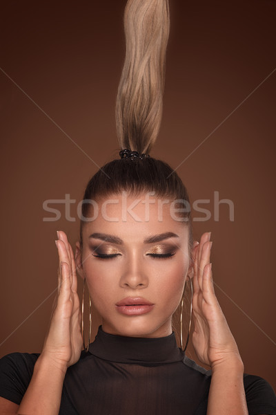 Stock photo: Face of attractive woman in golden makeup.