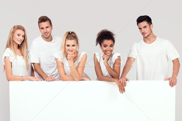 Csoport mosolyog emberek üres fehér tábla fiatal Stock fotó © NeonShot