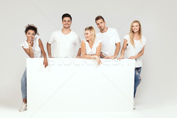 Stock photo: Group of smiling people with empty white board.