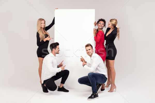 Group of elegant people with empty white board. Stock photo © NeonShot
