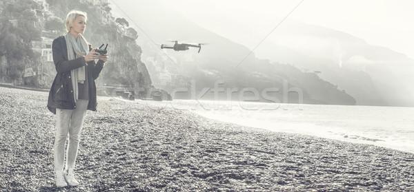 Young girl flying drone over italian coast. Stock photo © NeonShot