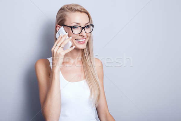 Young blonde woman talking by mobile phone. Stock photo © NeonShot