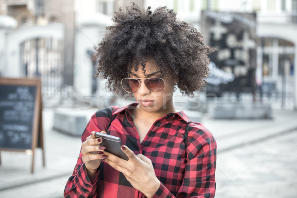 Girl with afro hairstyle using smart phone. Stock photo © NeonShot