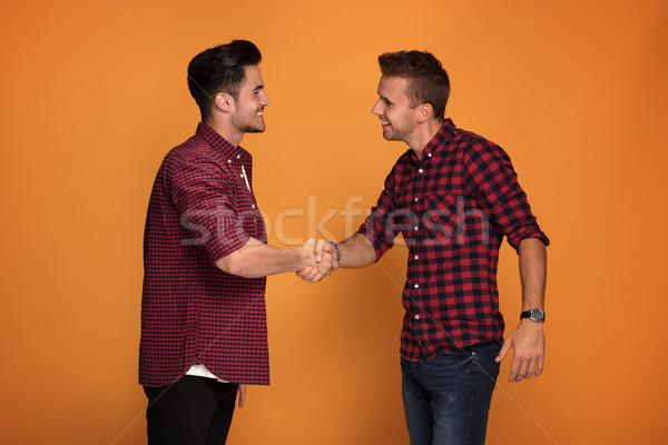Dos jóvenes guapo hombres apretón de manos mirando Foto stock © NeonShot