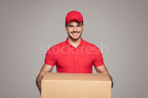 Smiling courier man holding a box package. Stock photo © NeonShot