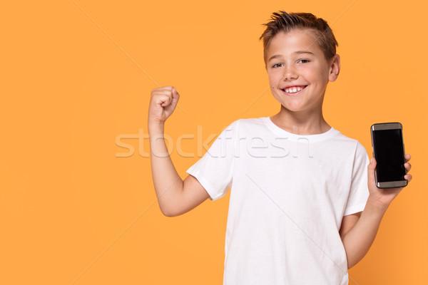 Peu garçon posant téléphone portable jeunes Photo stock © NeonShot