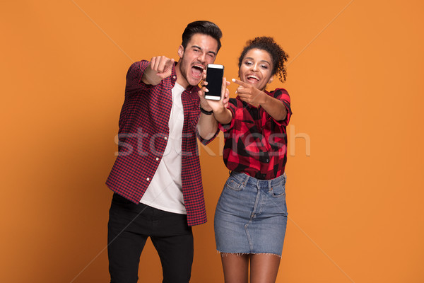 Smiling couple using mobile phone. Stock photo © NeonShot