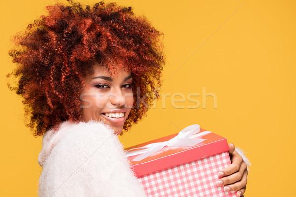 Afro girl posing with gift box, smiling. Stock photo © NeonShot
