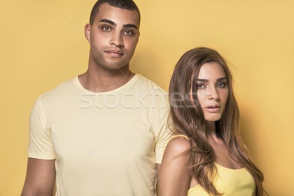 Beautiful couple posing on yellow background. Stock photo © NeonShot
