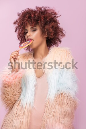 Fashionable afro woman with lollipop on pink background. Stock photo © NeonShot