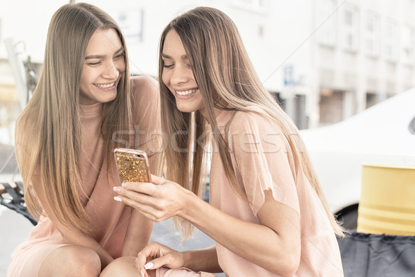 Two beautiful twins sisters spending time together. Stock photo © NeonShot