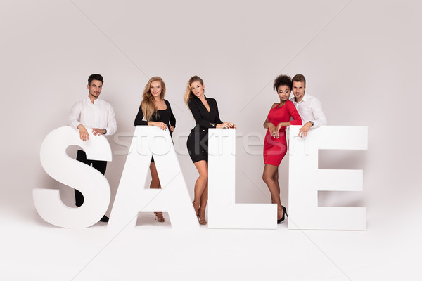 Group of elegant young people posing with sale letters. Stock photo © NeonShot