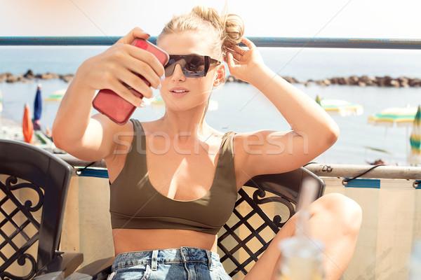 Girl taking self portrait photo with phone. Stock photo © NeonShot
