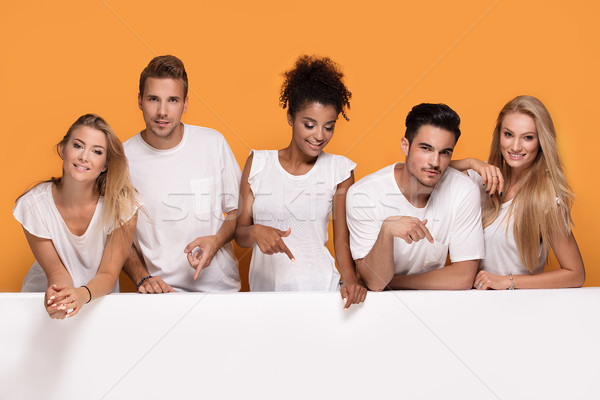 Five people posing with white empty board. Stock photo © NeonShot
