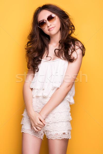 Young pretty girl posing on yellow background. Stock photo © NeonShot