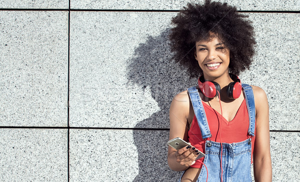 Girl with afro using mobile phone. Stock photo © NeonShot
