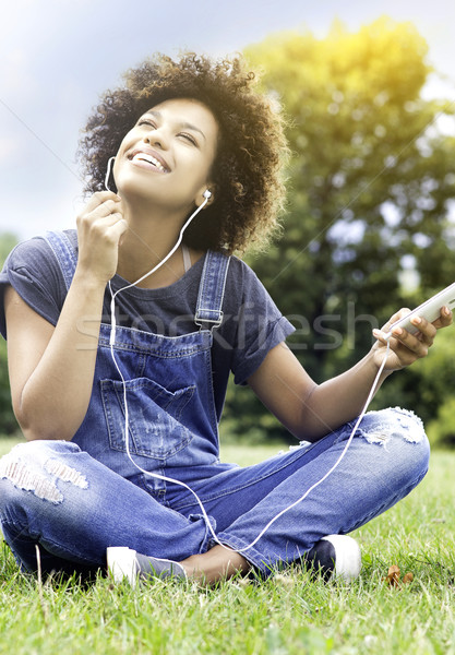 Young girl listening to music in park, relaxing. Stock photo © NeonShot