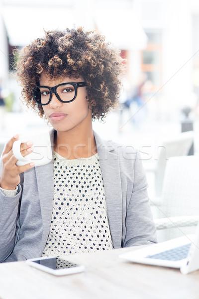 Stock photo: Elegant african american woman drinking coffee, working.