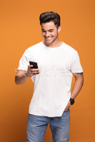 Smiling handsome man with mobile phone on yellow background. Stock photo © NeonShot