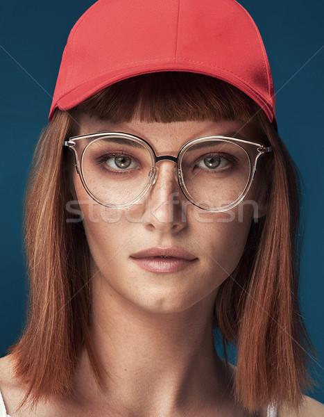 Divatos vörös hajú nő lány piros sapka szemüveg Stock fotó © NeonShot