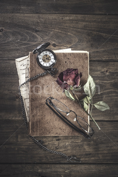 Still life with red rose on an old book placed with antique pock Stock photo © nessokv