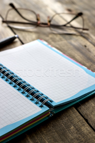 Spiral checked notebook  and spectacles on the background Stock photo © nessokv