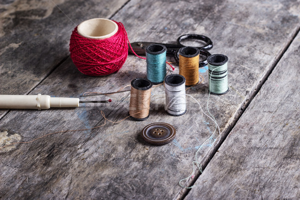 Many bobbin of thread with needle and button Stock photo © nessokv