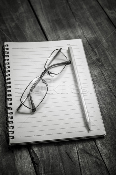 Black and white photo of notebook, pen and glasses on the table Stock photo © nessokv