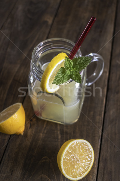 Lemonade glass jar with lemon wedges and straw Stock photo © nessokv